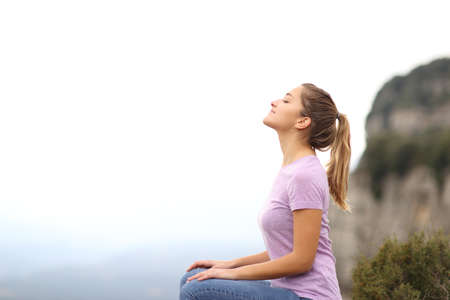 Side view portrait of a woman sitting breathing fresh air in the mountain Stok Fotoğraf