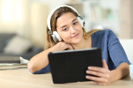Satisfied woman watching media on tablet wearing headphones at home