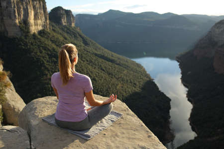 Back view portrait of a woman exercising yoga meditating in the mountain