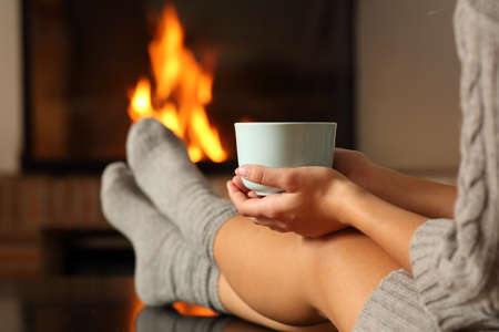 Close up of a woman with socks holding coffee cup in front a fireplace at home in winter