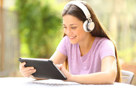 Happy woman with wireless headphones checking tablet content in a garden at home