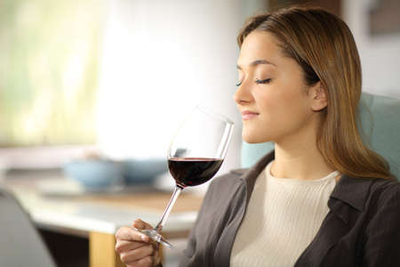 Serious woman smelling wine from cup sitting on a couch at home