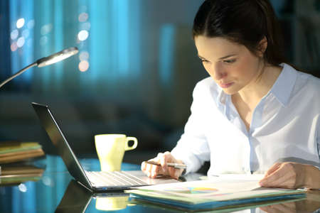Businesswoman comparing inform on laptop working in the night at homeoffice