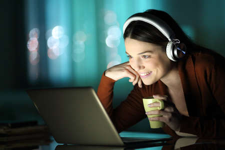 Happy lady watching videos on laptop sitting in the night at home