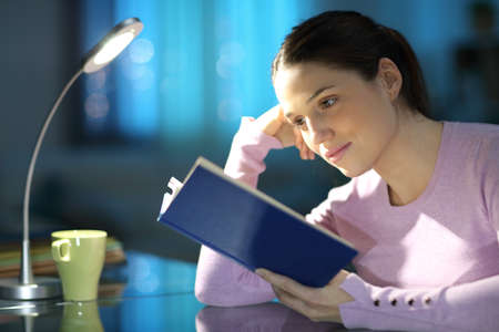 Concentrated woman reading a paper book at home in the night