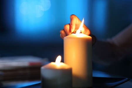 Close up of a woman hand lighting candle in the night at home Archivio Fotografico