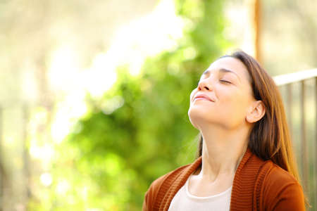Relaxed woman breathing fresh air in a garden a sunny day at home