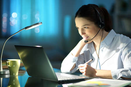 Happy tele operator working online with laptop and headset in the night at homeoffice Archivio Fotografico