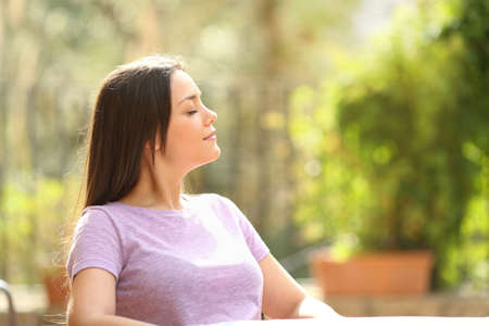 Profile of a woman relaxing enjoying fresh air sitting in a chair in a garden at home