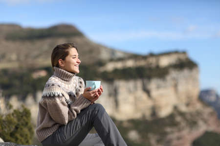 Happy trekker drinking coffee looking away contemplating views sitting in the mountain in winter