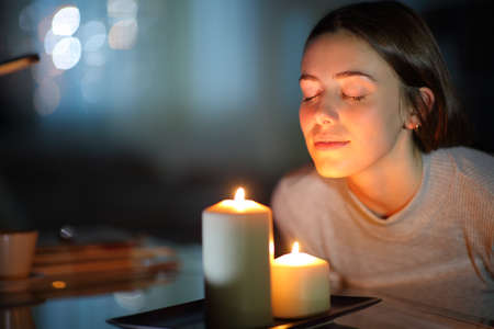 Relaxed woman smelling a lighted scented candle in the night at home Archivio Fotografico