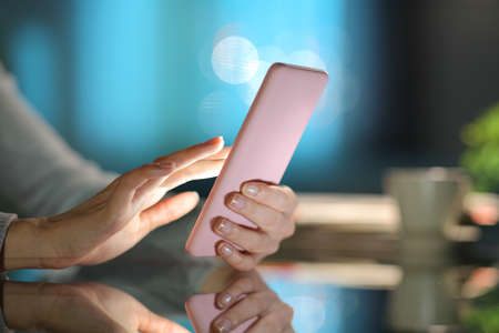 Close up of a woman hand using smart phone in the night at home