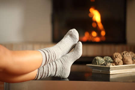 Close up of a woman legs with socks footresting in a fireplace in winter at home