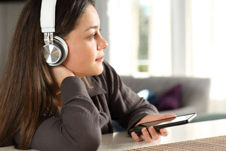 Pensive woman wearing wireless headphones contemplating listening to music at home Archivio Fotografico