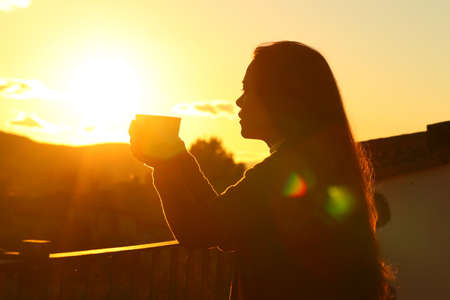 Backlight silhouette of a tenant drinking coffee contemplating sunset from a balcony Archivio Fotografico
