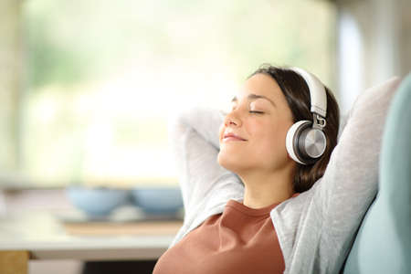 Carefree woman relaxing listening to music wearing headphones sitting on a sofa at home Archivio Fotografico
