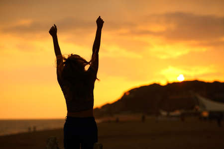 Back view portrait of a woman silhouette raising arms jumping celebrating at sunset on the beach