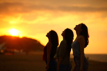 Silhouette of three friends breathing fresh air at sunset on the beach Archivio Fotografico