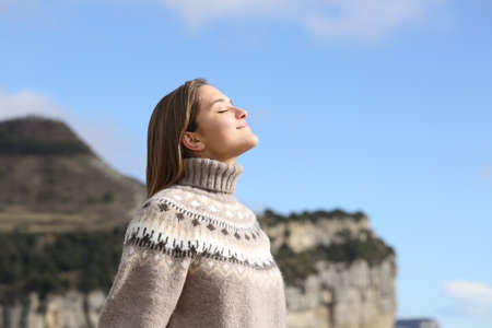 Side view portrait of a relaxed woman breathing fresh air in winter in the mountain Archivio Fotografico