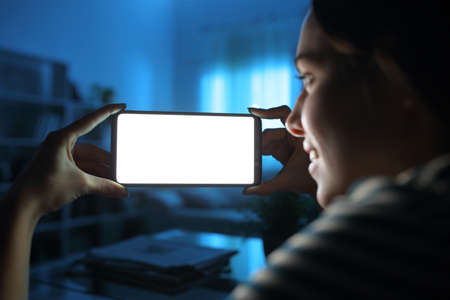 Close up of a lady hands showing and watching horizontal smart phone blank screen in the night at home
