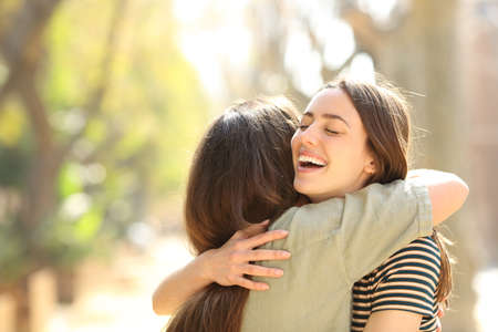Two happy women embracing after meeting in the street a sunny day