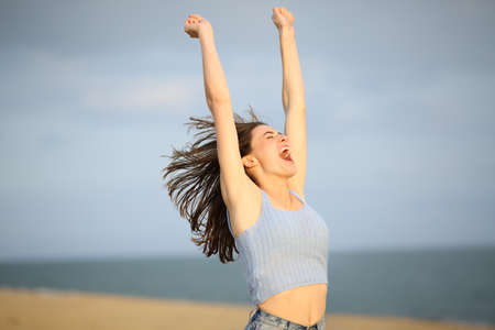 Excited woman celebrating summer vacation raising arms on the beach Archivio Fotografico