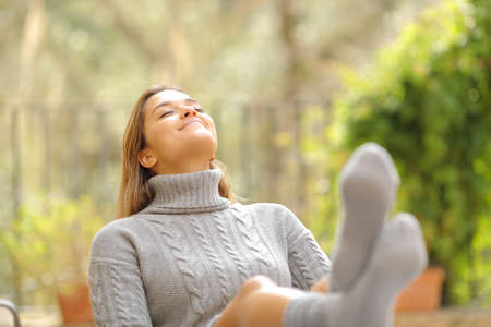 Happy woman resting seated in a chair breathing fresh air in a garden at home in winter Archivio Fotografico