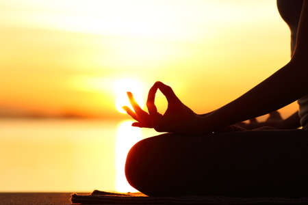 Backlight close up of woman silhouette doing yoga exercise at sunset on the beach