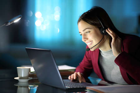 Happy telemarketer tele workingwith a laptop in the night at home or office