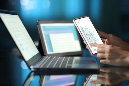 Close up of a woman hands using multiple devices at home in the night