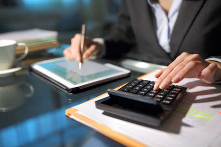 Close up of a businesswoman hands using tablet and calculator in the night at homeoffice