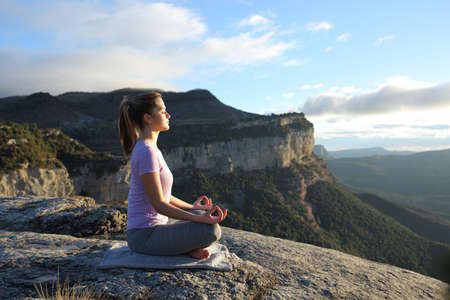 Profile of a woman doing yoga in the top of a cliff in the mountain