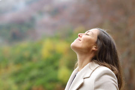 Profile of a satisfied middle aged woman breathing fresh air in a forest in winter
