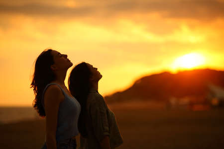 Profile of two women silhouette breathing fresh air at sunset on the beach Archivio Fotografico