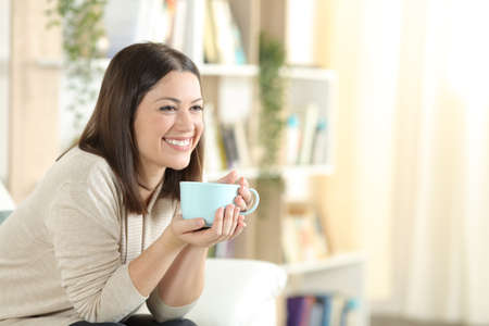 Happy woman smiling drinking coffee sitting on a couch in the living room at home