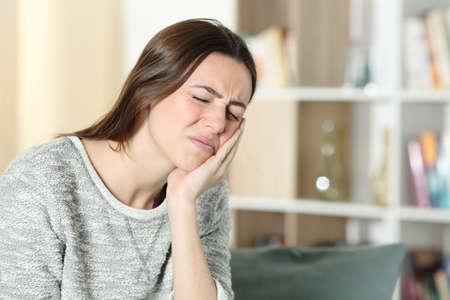 Stressed woman suffering toothache complaining touching cheek on a couch at home Standard-Bild