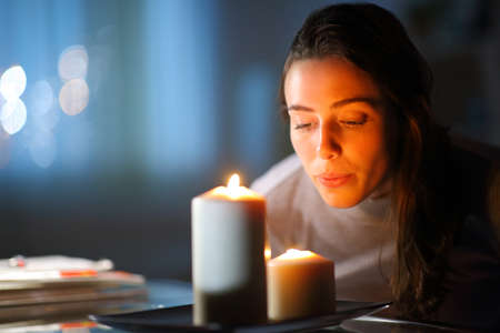 Beautiful woman blowing out candles in the living room at home in the night Archivio Fotografico