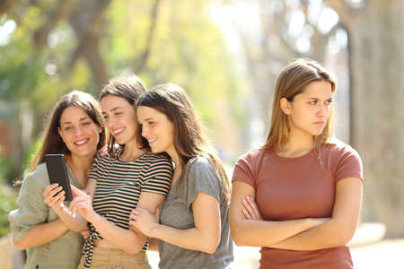Angry woman being ignored by her happy friends who are checking smart phone content in the street