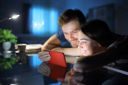 Happy couple watching media together on smart phone in the night at home Archivio Fotografico