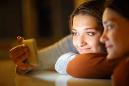 Couple of friends watching media on smart phone on a table in the night at home