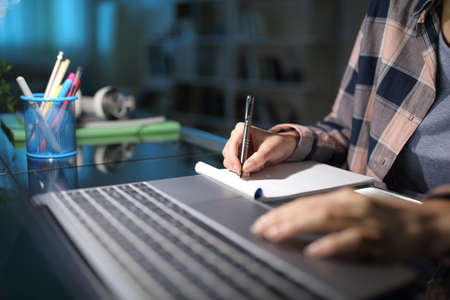 Close up of a student hand taking notes checking laptop in the night at home
