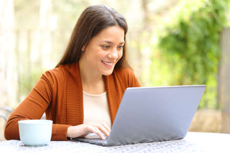 Happy woman browsing laptop content outdoors in a house terrace