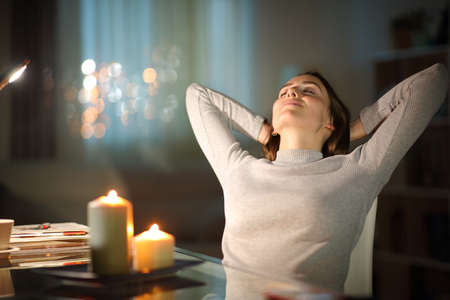 Relaxed woman resting sitting on a chair in the night with candles at home Archivio Fotografico