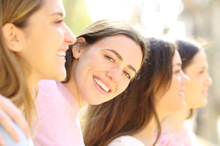 Happy woman with perfect smile posing between her friends in the street a sunny day Archivio Fotografico