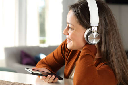 Happy lady with wireless headphones listening to music with smart phone at home