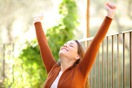 Excited woman celebrating happiness outdoors in a house terrace