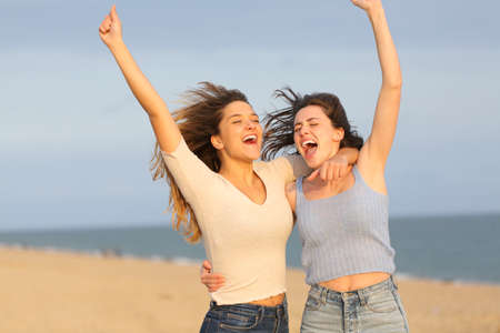 Two excited friends celebrating vacation jumping together on the beach