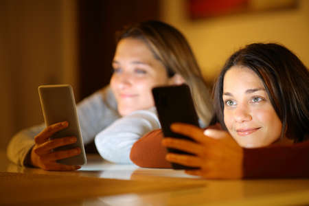 Two satisfied roommates ignoring each other using everyone her smart phone in the night at home