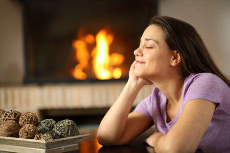 Happy tenant resting beside a fireplace in the living room at home Archivio Fotografico