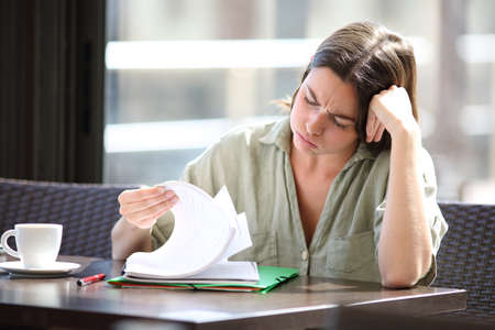 Frustrated student complaining checking a lot of notes to learn in a bar